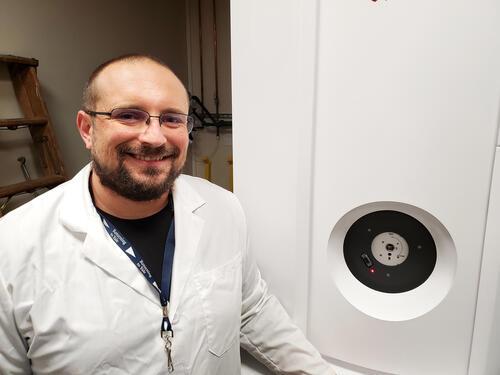 Man in lab coat in front of machine