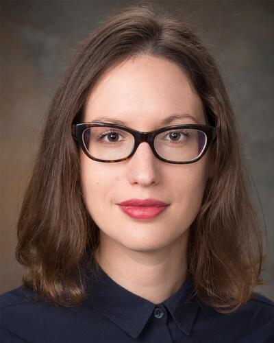 Portrait of a women wearing glasses, blouse, and lipstick