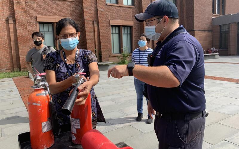 Man teaching woman how to use fire extinguisher