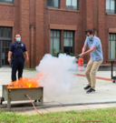 Man putting out controlled fire with fire extinguisher
