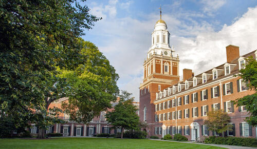 Brick building with steeple in courtyard with trees
